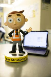 Photographie d'une figurine en premier plan avec en fond un ordinateur